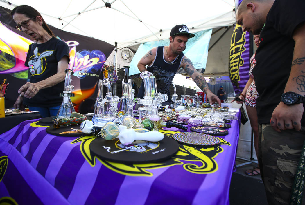 Mark of Official Genius, center right, shows off glassware products outside of Acres Cannabis during the first day of recreational sales in Las Vegas on Saturday, July 1, 2017. Chase Stevens Las V ...