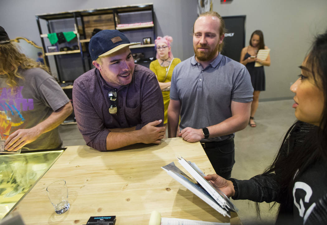 Jake Schlei, left, and Stephen Ward, both of Las Vegas, browse through edible marijuana products during the first day of recreational sales at Acres Cannabis in Las Vegas on Saturday, July 1, 2017 ...