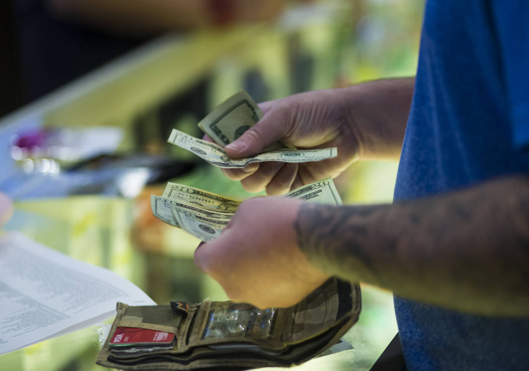 Henderson resident Ethan takes out cash to pay for marijuana products during the first day of recreational sales at Acres Cannabis in Las Vegas on Saturday, July 1, 2017. Chase Stevens Las Vegas R ...