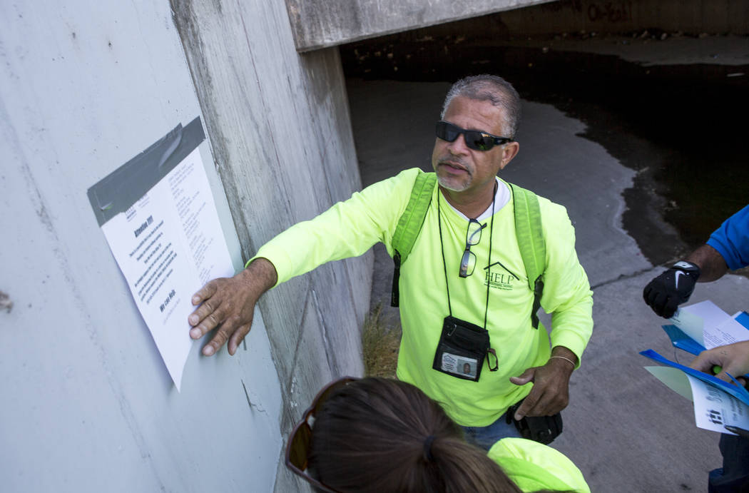 HELP of Southern Nevada employee Louis Lacey, the Mobile Crisis Intervention Team manager, puts up a sign warning the homeless about upcoming rain in monsoon season near flood tunnels under the Ha ...