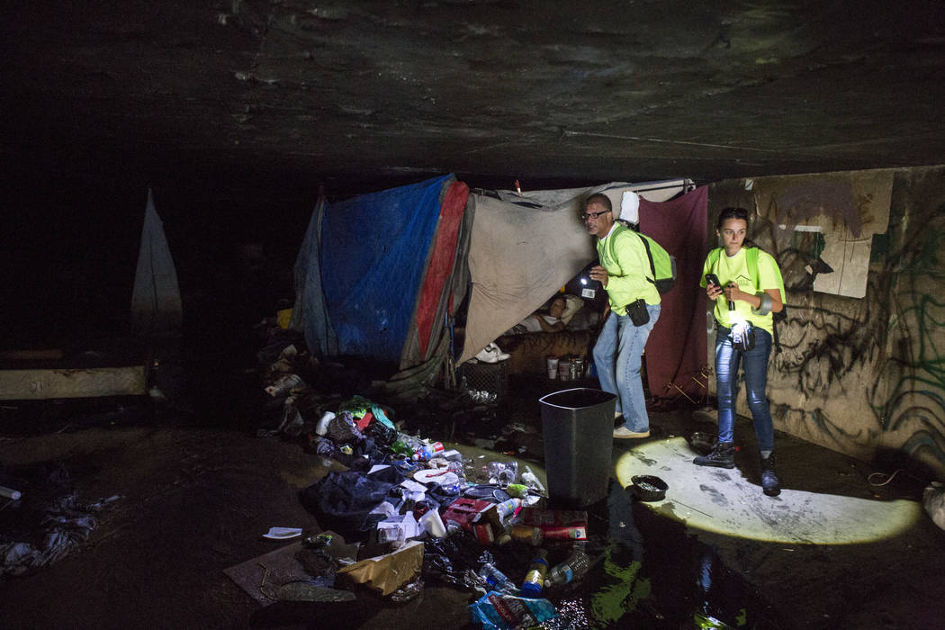 HELP of Southern Nevada employees Louis Lacey and Hayli Petcoff check on a homeless man in a flood tunnel near the Hard Rock hotel-casino on Tuesday, June 27, 2017.  Patrick Connolly Las Vegas Rev ...