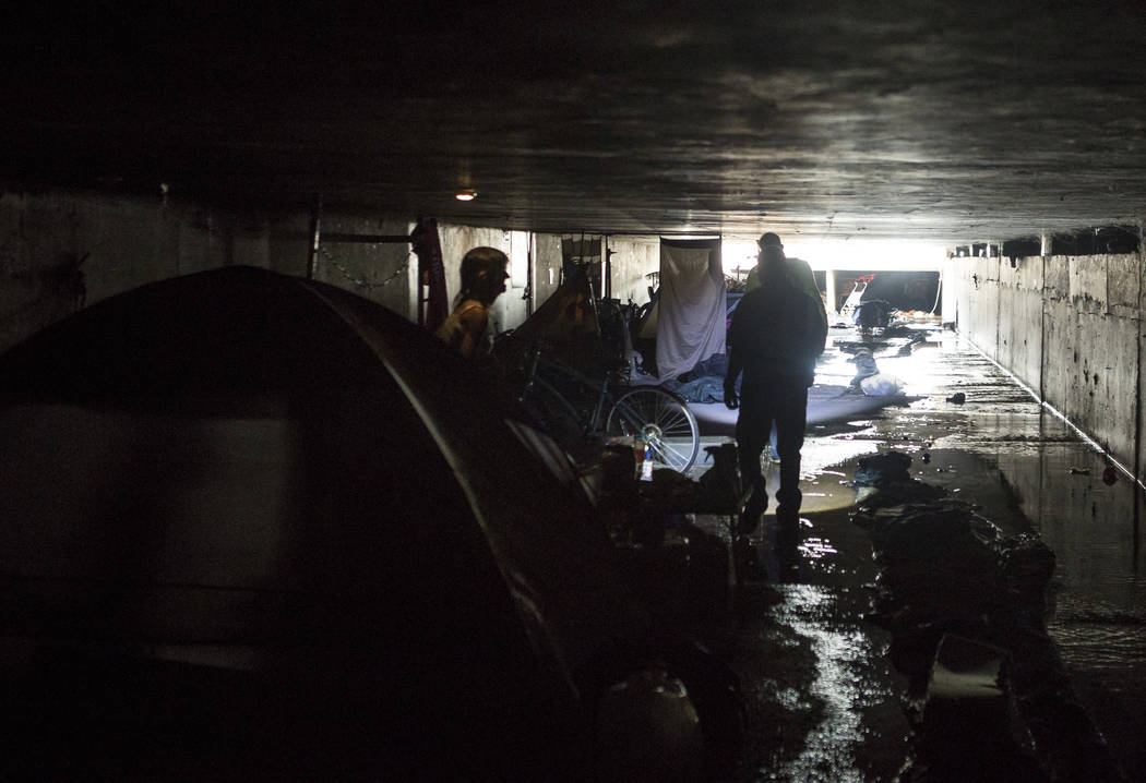 HELP of Southern Nevada employees Oscar Landgrabe, front right, and Louis Lacey ask Sheila North, left, if she needs help in flood tunnels near the Hard Rock hotel- casino on Tuesday, June 27, 201 ...