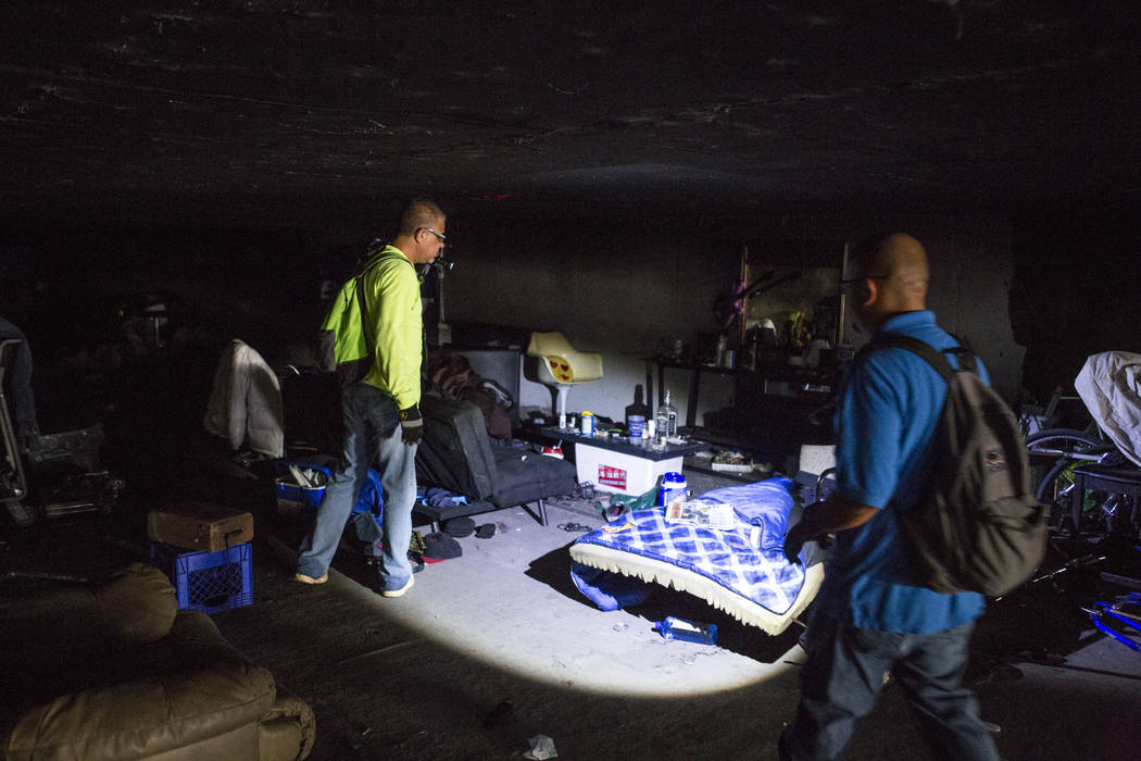 HELP of Southern Nevada employees Louis Lacey, left, and Oscar Landgrabe check out a vacant bed and makeshift coffee table in a flood tunnel near the Hard Rock hotel-casino on Tuesday, June 27, 20 ...