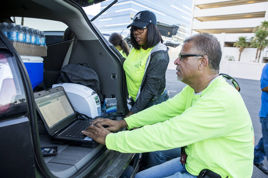 HELP of Southern Nevada employee Louis Lacey pulls up information for Sheila North while Denicia Rush stands by near the Hard Rock hotel-casino on Tuesday, June 27, 2017.  Patrick Connolly Las Veg ...