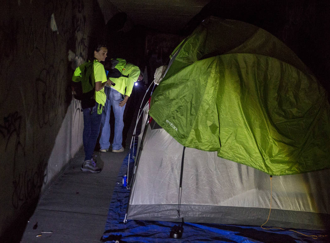 HELP of Southern Nevada employees Louis Lacey and Hayli Petcoff peer into a vacant tent in a flood tunnel near the Hard Rock  hotel-casino on Tuesday, June 27, 2017.  Patrick Connolly Las Vegas Re ...