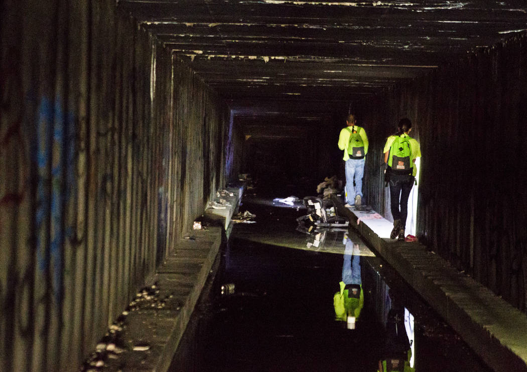 HELP of Southern Nevada employees Louis Lacey, front, and Hayli Petcoff lead the way and avoid sitting water along the side of a flood tunnel near the Hard Rock hotel-casino on Tuesday, June 27, 2 ...