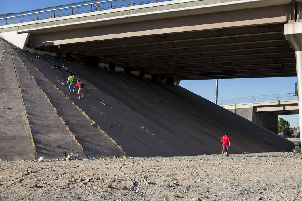 HELP of Southern Nevada employee Louis Lacey, the Mobile Crisis Intervention Team manager, climbs up an underpass beneath Interstate 15 while U.S. Vets team members follow near the Rio hotel-casin ...