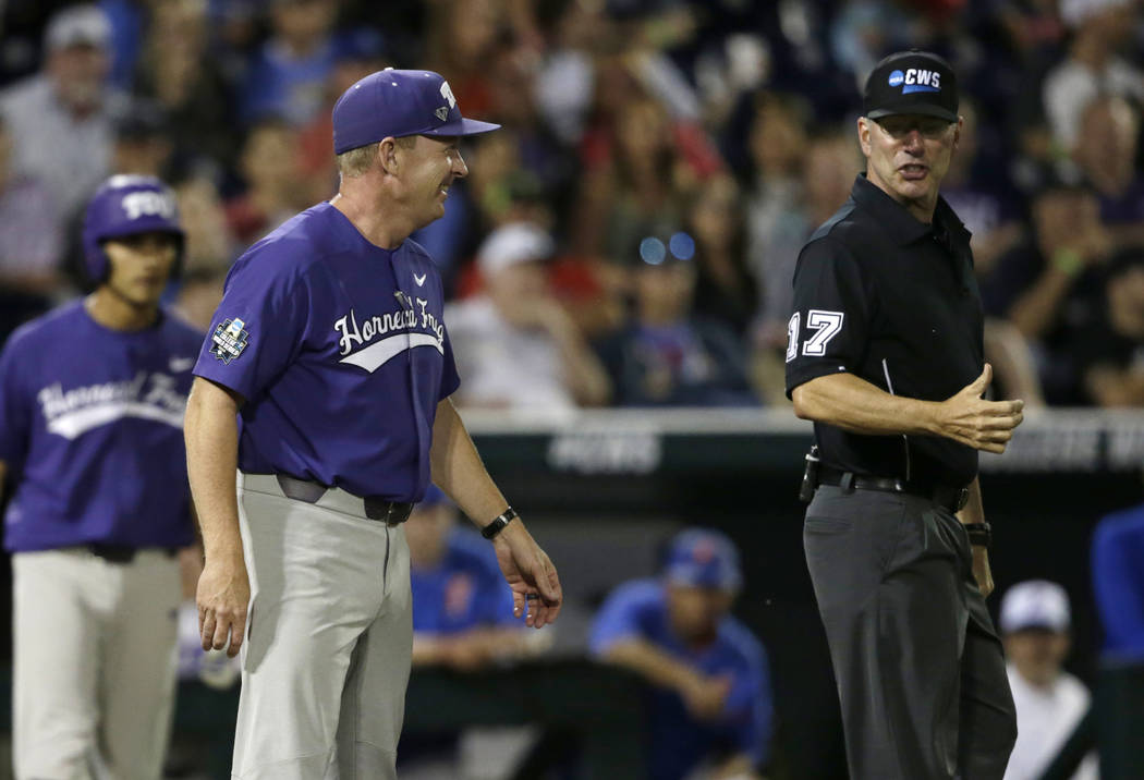 TCU coach Jim Schlossnagle, center, goes out to talk to home plate umpire Steve Mattingly, right, about a ball hit by Elliott Barzilli for a foul ball in the seventh inning of an NCAA College Worl ...