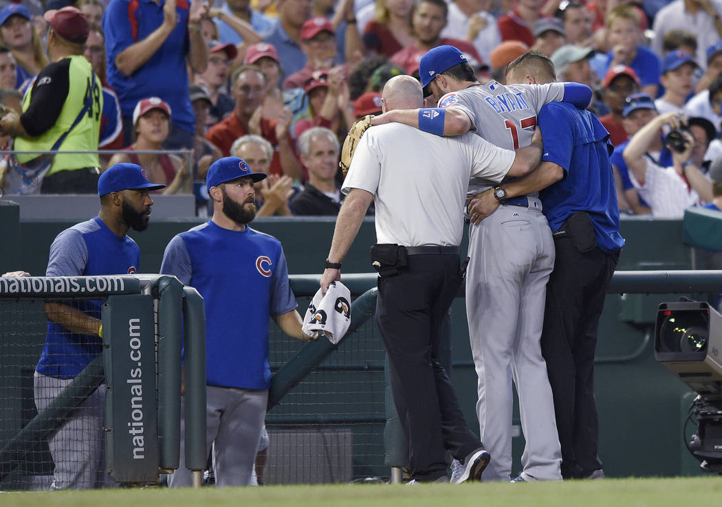 Chicago Cubs third baseman Kris Bryant (17) is helped off the field by trainers after he was injured during the fifth inning of the team's baseball game against the Washington Nationals, Wednesday ...