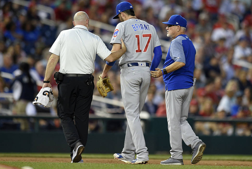 Chicago Cubs third baseman Kris Bryant (17) is helped off the field by a trainer and Chicago Cubs manager Joe Maddon, right, after he was injured during the fifth inning of the team's baseball gam ...