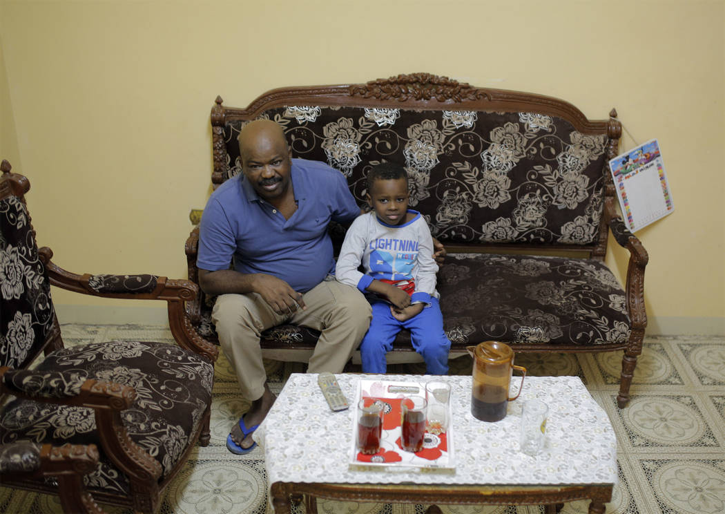 Sudanese activist Tayeb Ibrahim, who had worked to expose Sudanese abuses in the volatile South Kordofan province and hopes to see family living in Iowa, watches television with his son Mohammed i ...