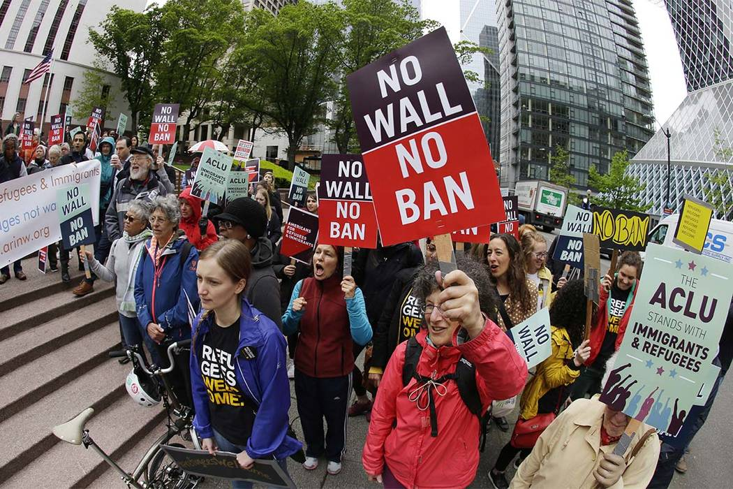In this May 15, 2017 file photo, protesters wave signs and chant during a demonstration against President Donald Trump's revised travel ban, outside a federal courthouse in Seattle. The Supreme Co ...