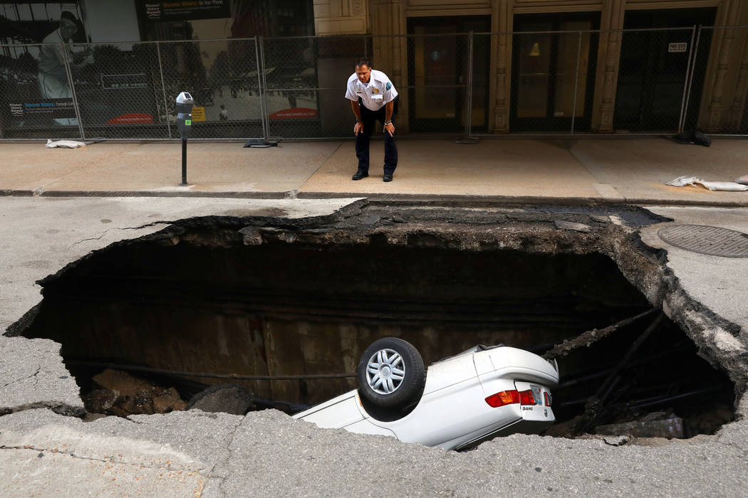 A St. Louis police officer looks over a large hole in 6th Street, Thursday, June 29, 2017, in St. Louis, that swallowed a Toyota Camry between Olive and Locust Streets. It isn't immediately clear  ...