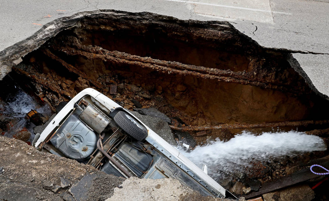 A Toyota Camry sits in a large hole in 6th Street, Thursday, June 29, 2017, in St. Louis. It isn't immediately clear what caused the collapse. (Christian Gooden/St. Louis Post-Dispatch via AP)