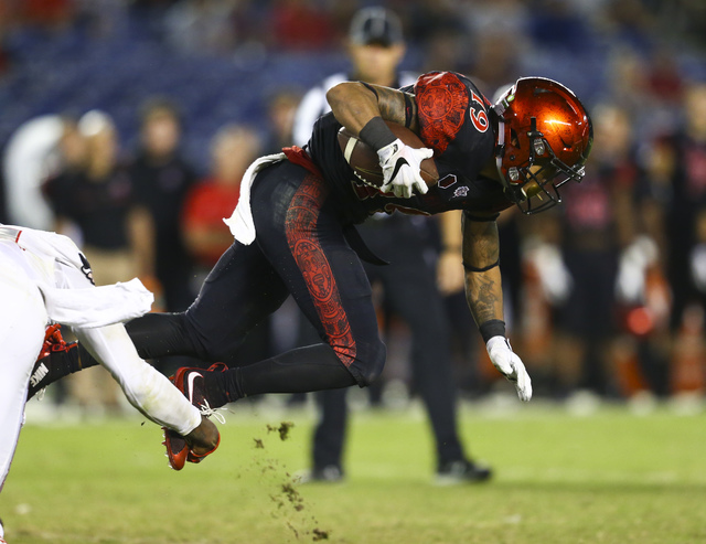San Diego State running back Donnel Pumphrey (19) is tripped up by UNLV defense during a football game at Qualcomm Stadium in San Diego on Saturday, Oct. 8, 2016. San Diego State won 26-7 over the ...