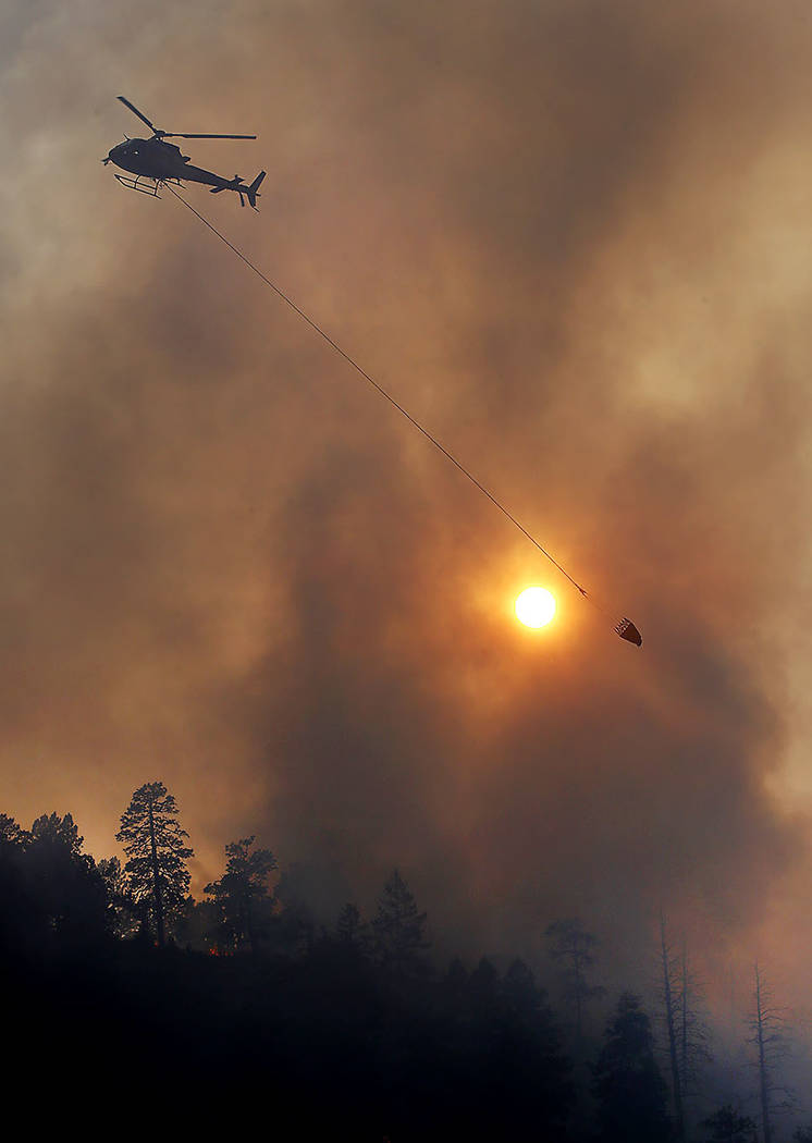 A helicopter drops water on the Lightner Creek Fire on Lightner Creek Road west of Durango, Colo., on Wednesday, June 28, 2017.  The wildfire in southwestern Colorado has burned at least one home  ...