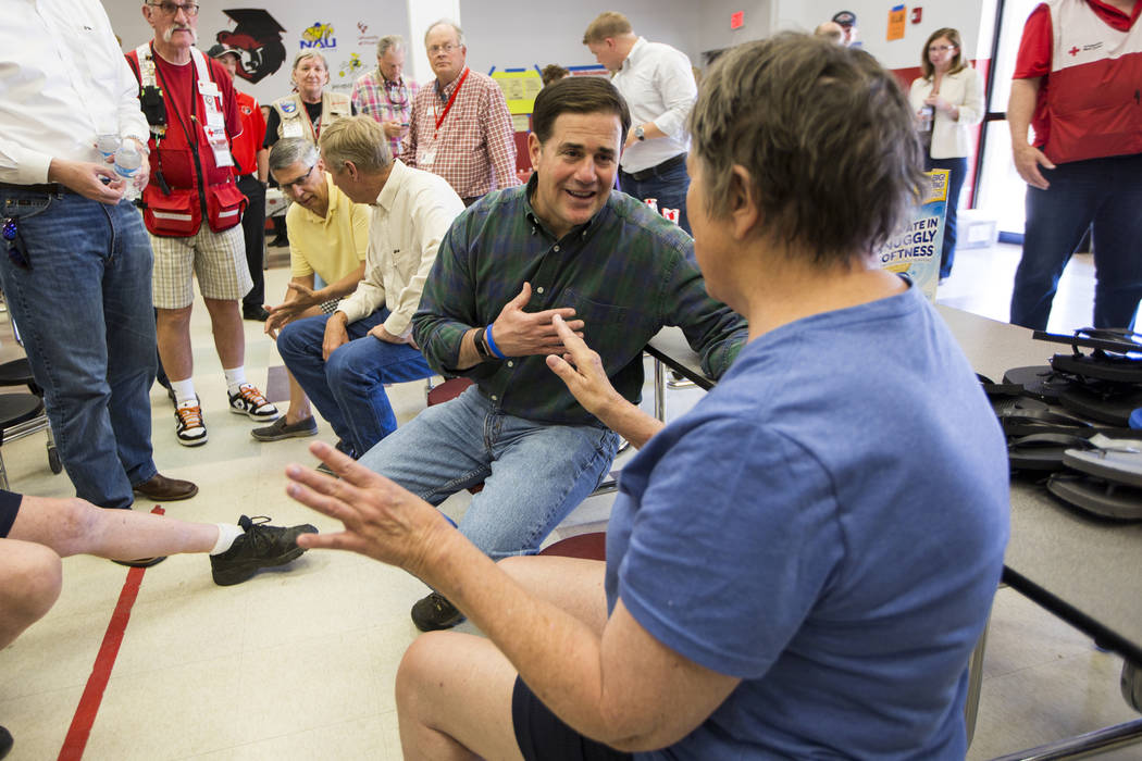 Arizona Gov. Doug Ducey speaks with Jean Wilson, a 71-year-old evacuee from the community of Pine Flats at the fire's evacuation center on Thursday, June 29, 2017, in Prescott Valley, Ariz. Crews  ...