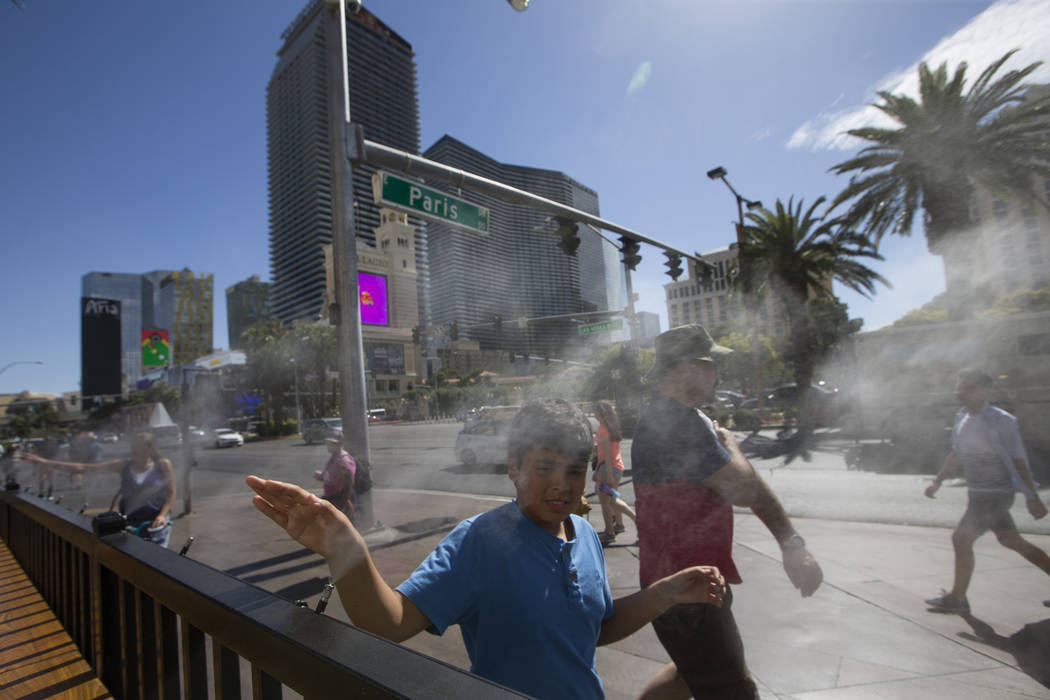 Pedestrians cool off on water misters along the Las Vegas Strip. (Richard Brian/Las Vegas Review-Journal) @vegasphotograph