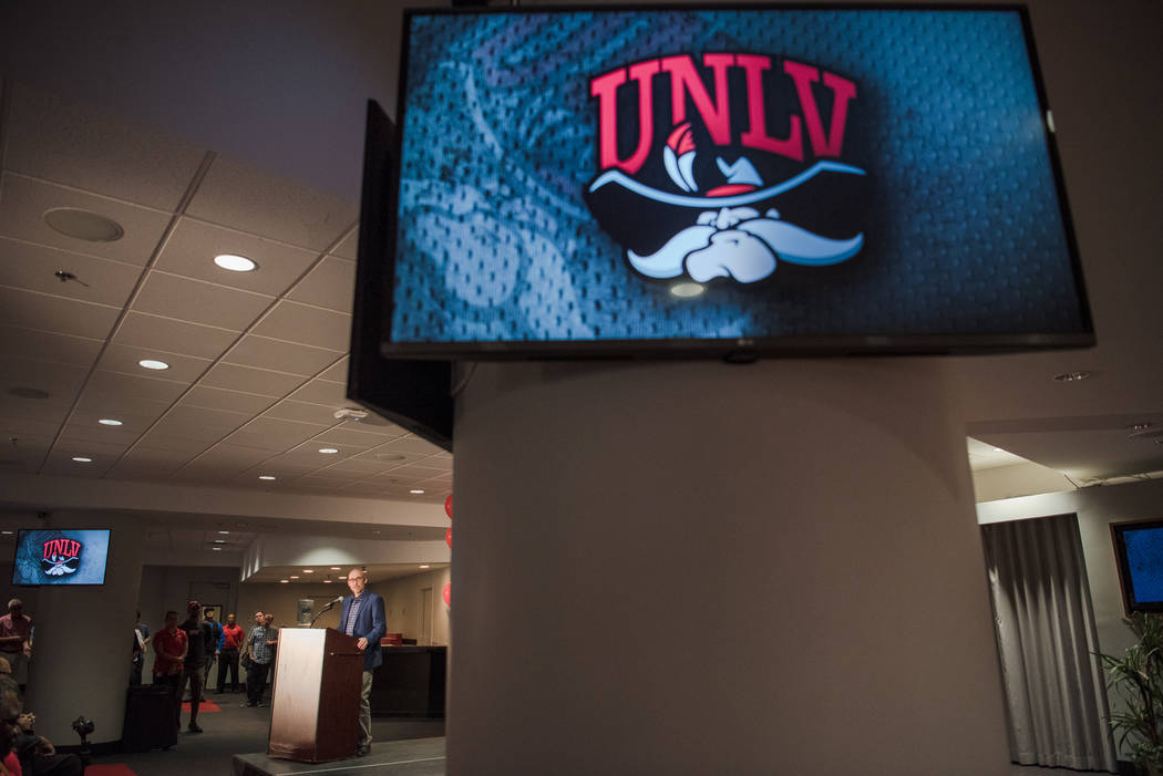 Dan Price, President of Adrenalin Inc., discusses the design process of the new UNLV logo at the UNLV Thomas & Mack Center, with the old logo on display on the monitors, on Wednesday, June 28. ...