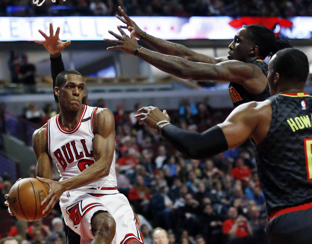 Chicago Bulls guard Rajon Rondo (9) looks to pass against Atlanta Hawks guard Dennis Schroder, forward Taurean Prince and center Dwight Howard during the first half of an NBA basketball game Satur ...