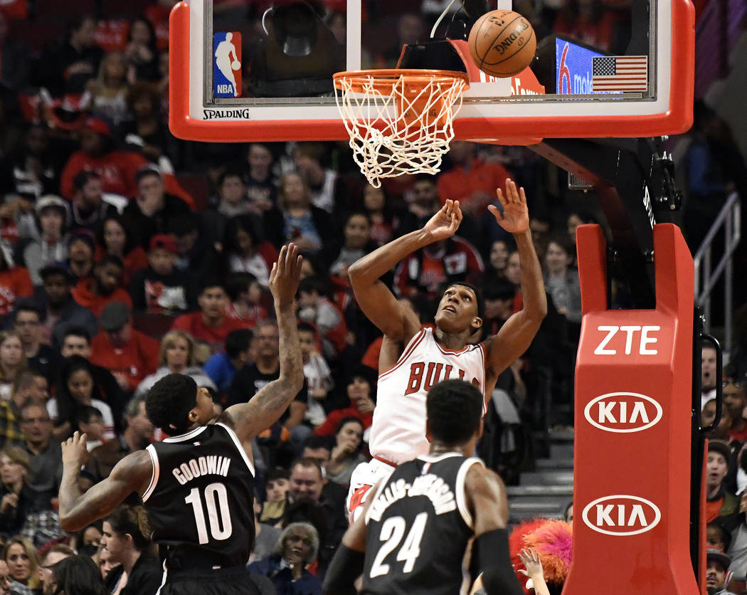 Chicago Bulls guard Rajon Rondo, rear, watches his shot as Brooklyn Nets guard Archie Goodwin (10) defends during the second half of an NBA basketball game in Chicago, Wednesday, April 12, 2017. T ...