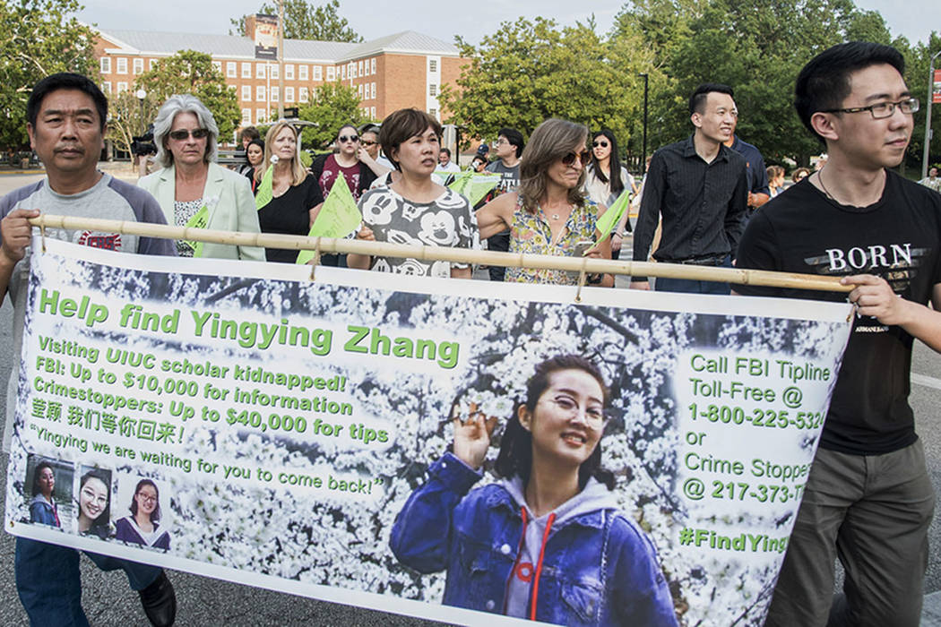 Yingying Zhang's father Ronggao Zhang, left, and her friend Xiaolin Hou carry the banner as community members join together to walk for Yingying, a Chinese scholar who went missing three weeks ago ...