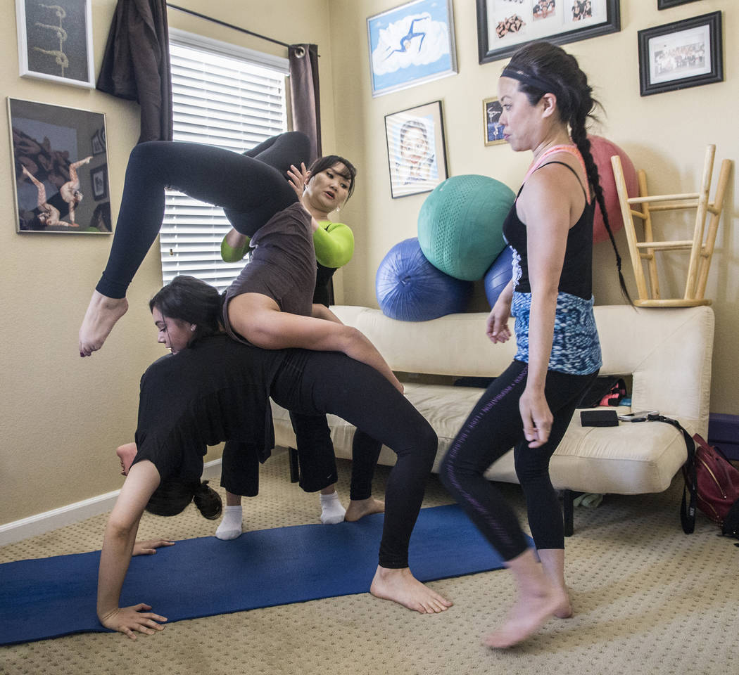 Otgo Waller, middle/back, helps Ariana Sokol, middle, and Victoria Niederhoffer, below, stretch during a training session at her home studio on Tuesday, June 13, 2017, in Las Vegas. Waller is a co ...