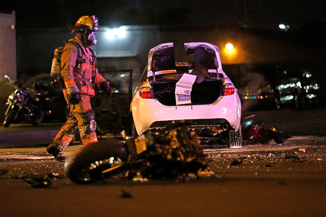 A firefighter works at a crash scene at W. Charleston Boulevard and Arville Street in Las Vegas, Wednesday, Feb. 15, 2017.  (Chitose Suzuki/Las Vegas Review Journal)