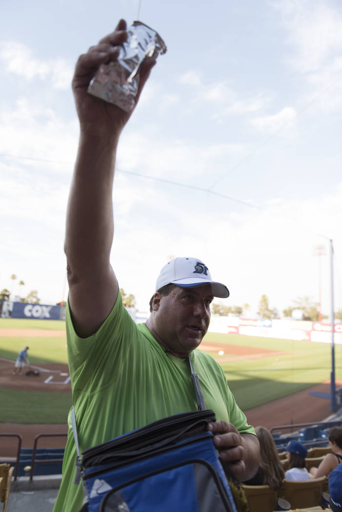 Hawker Bruce Reiner holds up a hot dog as he walks through the stands with more than 50 pounds of merchandise prior to a Las Vegas 51s baseball game at Cashman Field in Las Vegas Monday, June 27,  ...
