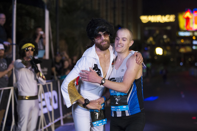 First place runner Michael Wardian, left, and third place runner Chip O'hara, embrace after the Rock-n-Roll Marathon at the Strip near The Mirage hotel-casino on Sunday, Nov. 13, 2016, in Las Vega ...