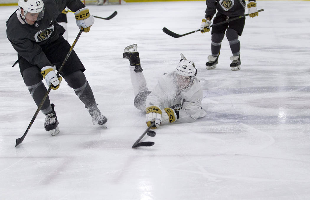 Patrick Bajkov, center, reaches for the puck after tripping during the Vegas Golden Knights Development Camp at the Las Vegas Ice Center in Las Vegas on Saturday, July 1, 2017. Richard Brian Las V ...