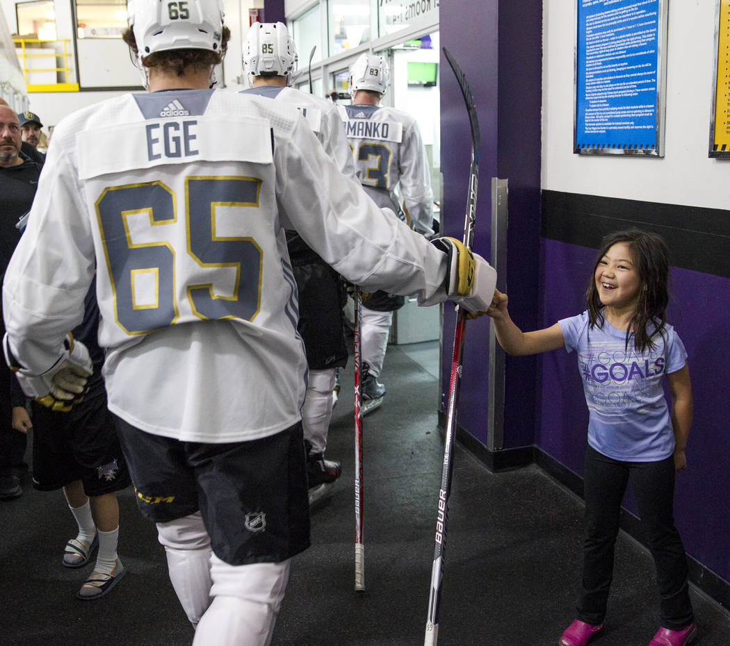 Las Vegas resident and youth hockey player Ella Long, 7, fist bumps with Wyatt Ege during the Vegas Golden Knights Development Camp at the Las Vegas Ice Center in Las Vegas on Saturday, July 1, 20 ...