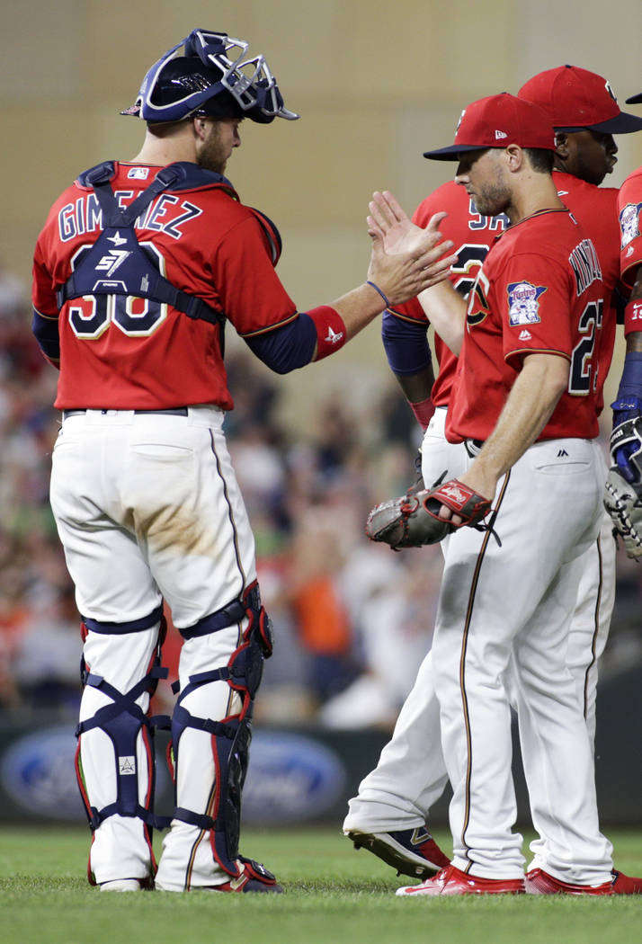 Minnesota Twins relief pitcher Brandon Kintzler is congratulated by teammate Chris Gimenez after the Twins defeated the Baltimore Orioles 9-6 in a baseball game, Friday, July 7, 2017, in Minneapol ...