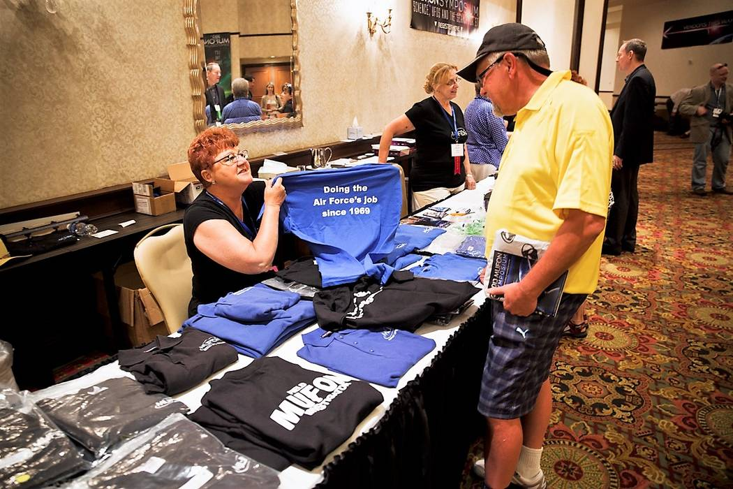 Mutual UFO Network volunteer Sharon McGee holds up a T-shirt at the 2013 MUFON symposium at the JW Marriott resort in Las Vegas. (Handout)