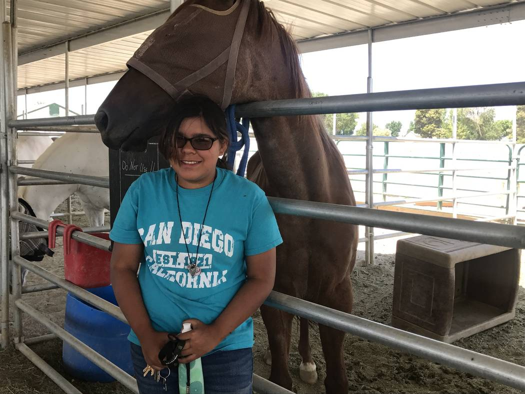 "The Horses4Heroes youngest summer camp counselor Ava ""Nina Valenzuela, 13, is greeted by a horse June 27 at the Horeses4Heroes Community Equestrian Center at Floyd Lamb Park at Tule Springs. (Kail ..."