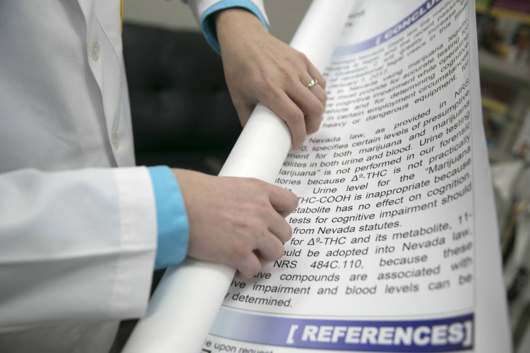 Graham Lambert rolls up his and Charles Cullison's proposal for standardizing blood samples for marijuana DUI testing at the Touro University campus in Henderson, Thursday, June 29, 2017. (Gabriel ...