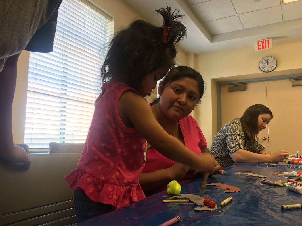 Dalila Santos does arts and crafts with Angelie, her 1-year-old daughter, during the exploration lab program at the Clark County Library on June 26, 2017.  The Clark County Library expands on thei ...