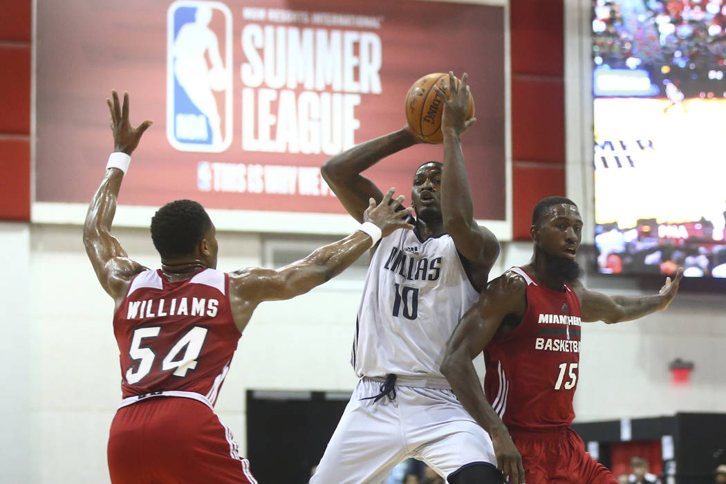 Dallas Mavericks' Dorian Finney-Smith (10) drives between Miami Heat's Matt Williams (54) and Okaro White (15) during a basketball game at the NBA Summer League at the Thomas & Mack Center in  ...