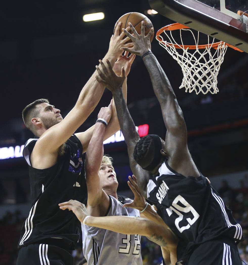 Sacramento Kings' Georgios Papagiannis (13) and JaKarr Sampson (29) reach for a rebound against Milwaukee Bucks' Tim Kempton (32) during a basketball game at the NBA Summer League at the Thomas &a ...