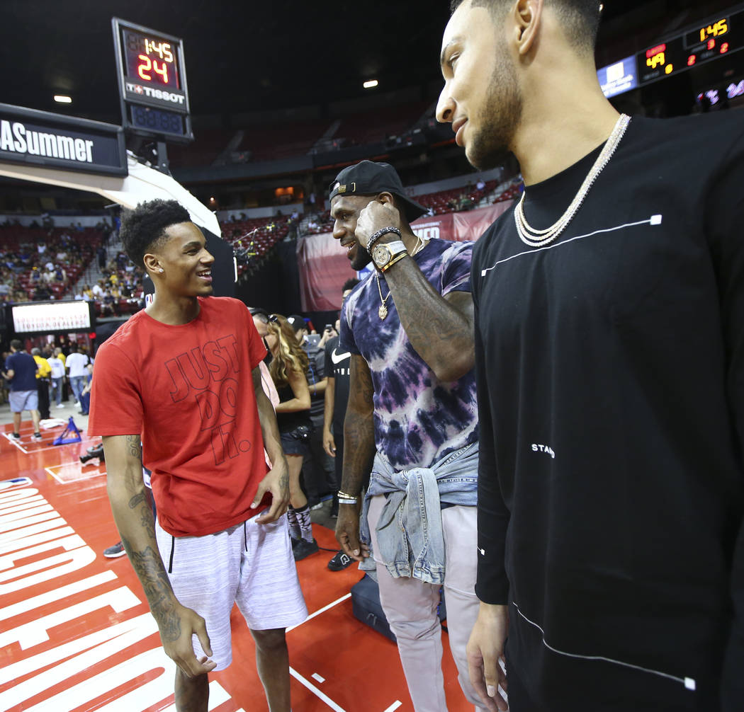 Dejounte Murray, from left, talks with LeBron James and Ben Simmons at halftime as the Los Angeles Lakers play the Philadelphia 76ers in a basketball game at the NBA Summer League at the Thomas &a ...