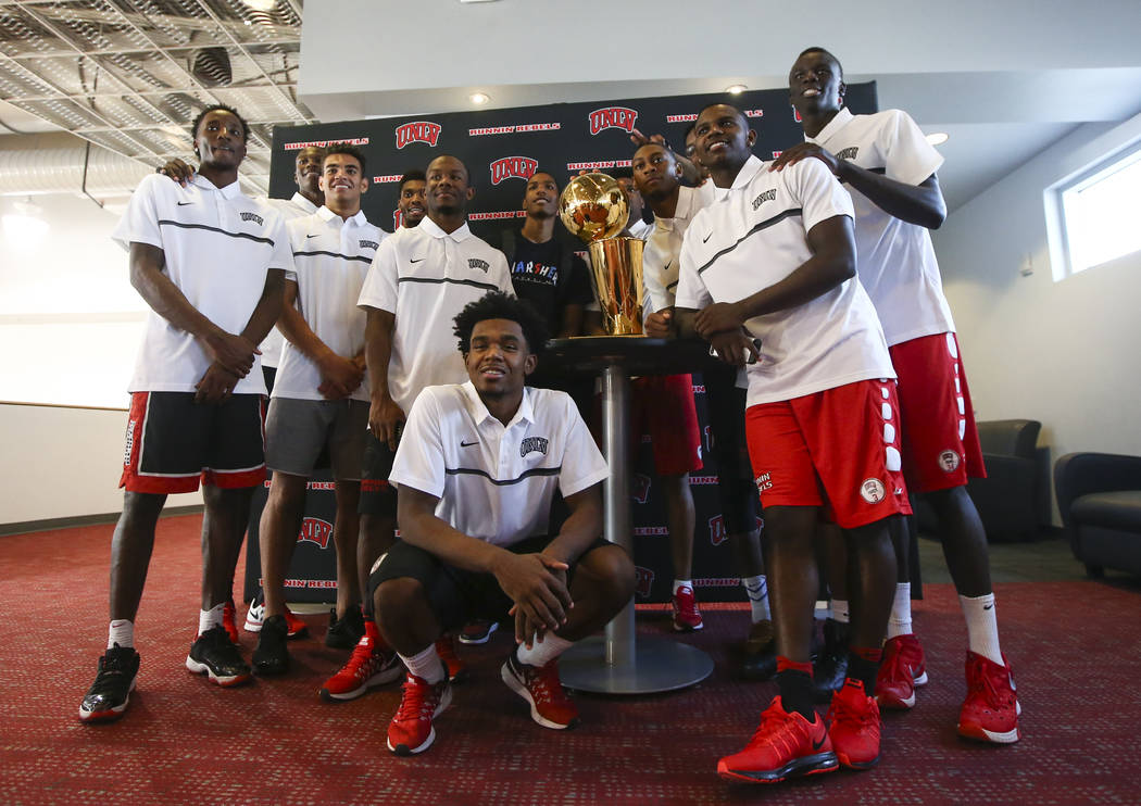 UNLV basketball players, along with former Rebel and current Golden State Warriors player Patrick McCaw, left of trophy, pose with the Larry O'Brien Trophy in Mendenhall Center at UNLV in Las Vega ...
