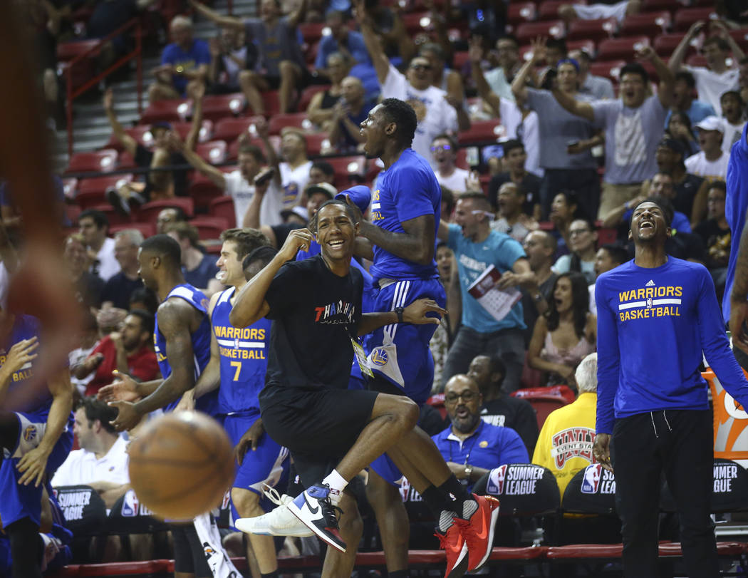 Golden State Warriors' Patrick McCaw, wearing black, reacts with the bench after a three-pointer from Golden State Warriors' Dylan Ennis during a basketball game against the Los Angeles Clippers a ...