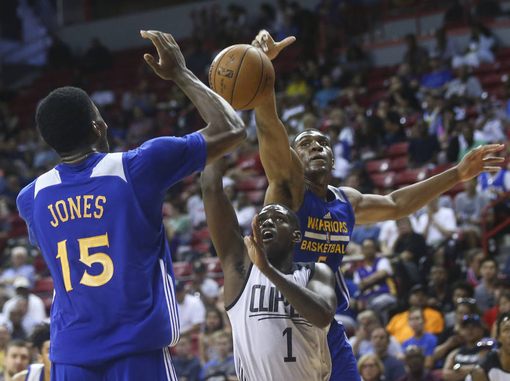 Los Angeles Clippers' Jawun Evans (1) is blocked by Golden State Warriors' Kevon Looney, right, with the help of teammate Damian Jones (15) during a basketball game at the NBA Summer League at the ...