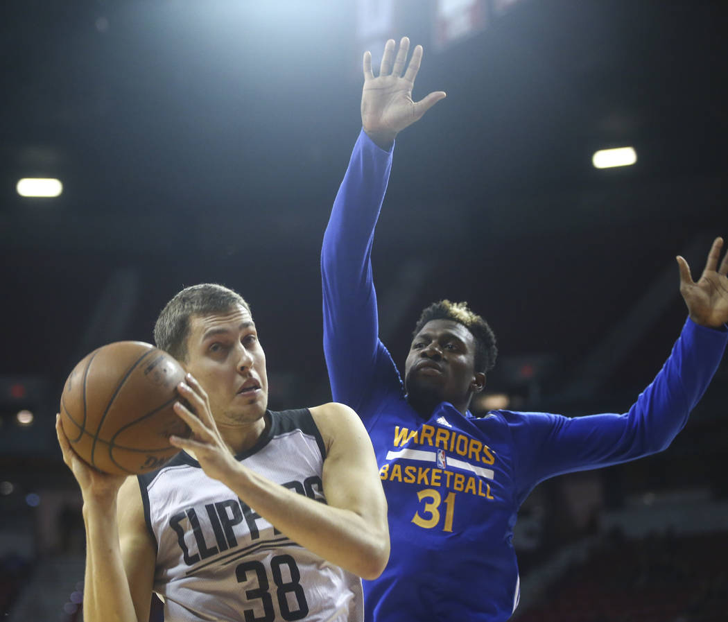 Los Angeles Clippers' Kyle Wiltjer (38) gets a rebound in front of Golden State Warriors' Dylan Ennis (31) during a basketball game at the NBA Summer League at the Thomas & Mack Center in Las  ...