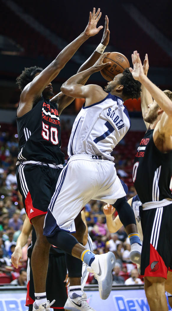 Memphis Grizzlies player Wayne Selden Jr. up against Portland Trail Blazers forward Caleb Swanigan and forward Jake Layman during the NBA Summer League semifinal basketball game at Thomas and Mack ...