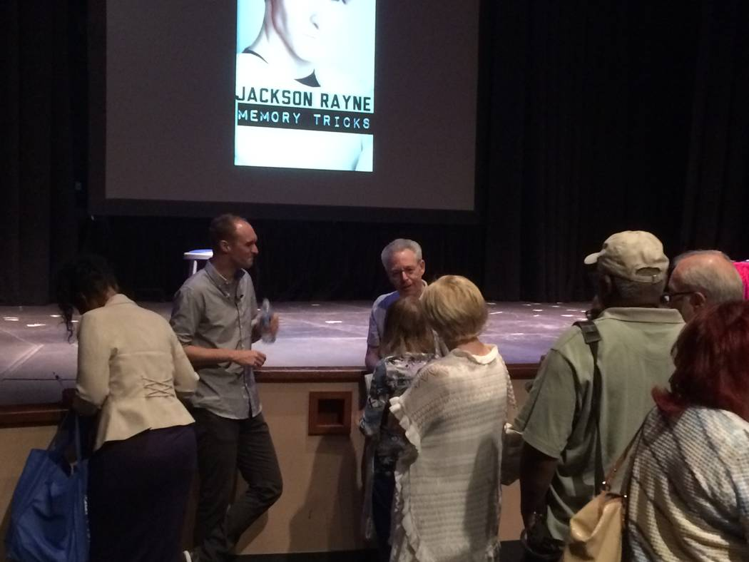 Jackson Rayne, leaning on stage, speaks one-on-one with audience members April 30, 2017, after his talk at Summerlin Library. His topic was Memory Tricks and he showed attendees how to que their b ...