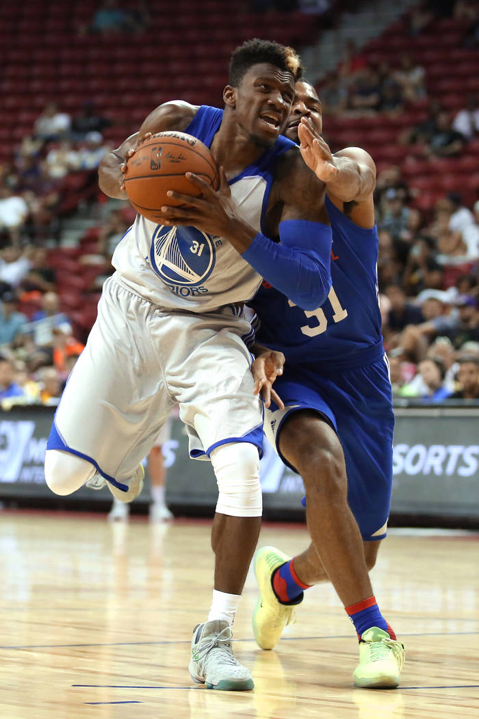 Golden State Warriors guard Dylan Ennis brings the ball to the basket as Philadelphia 76ers guard Aaron Harrison attempts to block during the Warriors NBA Summer League game against the 76ers ...