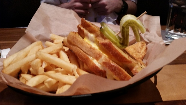 Grilled cheese, made with cheddar, Swiss, mozzarella and Jack cheeses melted between Parmesan sourdough, is shown with fries at Lazy Dog. (File)