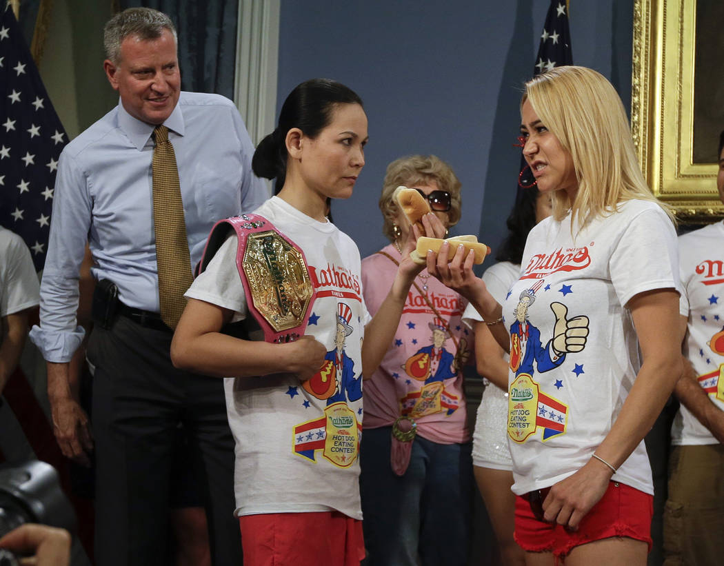 CORRECTS POSITION OF THOMAS AND SUDO- New York City Mayor Bill de Blasio watches hot dog eating contestants Sonya Thomas, left, and Miki Sudo, right, during a news conference to promote the upcomi ...