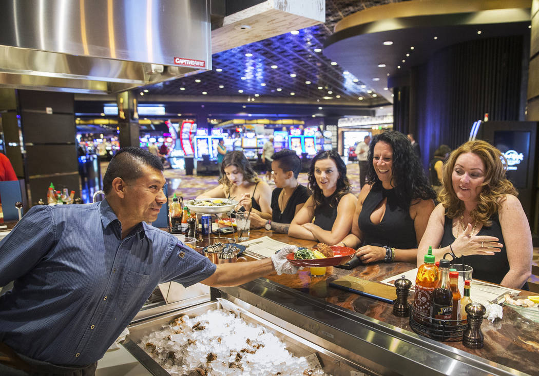 Server Matias Perez, left, serves crab cakes to dinner guests at Oyster Bar on Wednesday, June 29, 2017, at the Hard Rock hotel-casino, in Las Vegas. Benjamin Hager Las Vegas Review-Journal @benja ...